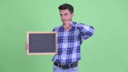 anız : Stressed young Hispanic man holding blackboard and giving thumbs down