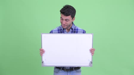 Stressed young Hispanic man holding white board and getting bad news