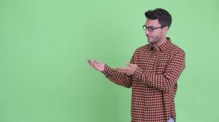 Stressed young Hispanic hipster man showing something and giving thumbs down