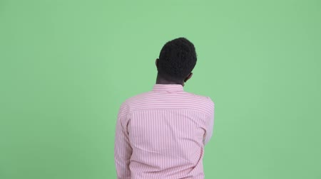 direkt : Rear view of young African businessman pointing finger