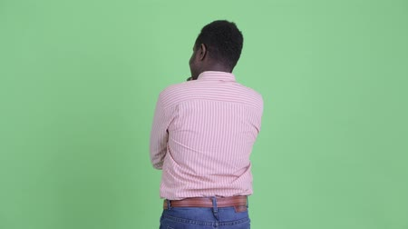 looking far away : Rear view of young African businessman thinking and waiting