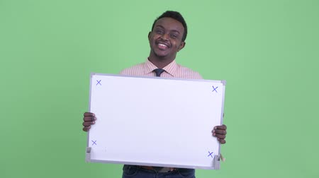 placa : Happy young African businessman thinking while holding white board