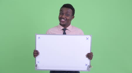 placa : Happy young African businessman holding white board and looking surprised