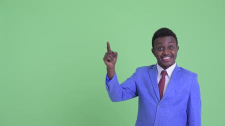 algo : Happy young African businessman pointing up and looking excited