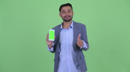 mustache : Happy young bearded Persian businessman showing phone and giving thumbs up Stock Footage
