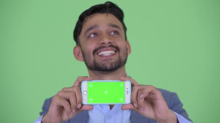 mustache : Face of happy young bearded Persian businessman thinking while showing phone
