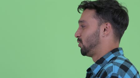 ближневосточный : Profile view of happy young bearded Persian hipster man being interviewed
