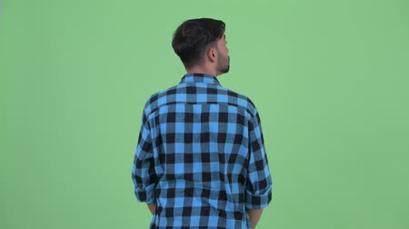 looking far away : Rear view of young bearded Persian hipster man thinking and looking around