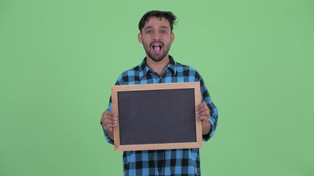 choque : Happy young bearded Persian hipster man holding blackboard and looking surprised