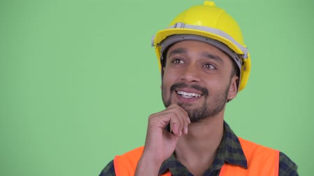 mustache : Face of happy young bearded Persian man construction worker thinking and looking up Stock Footage