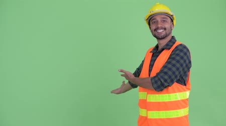 mustache : Happy young bearded Persian man construction worker showing to the back Stock Footage