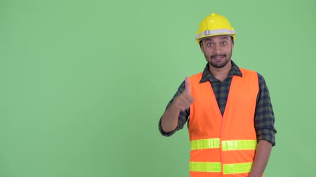hardhat : Happy young bearded Persian man construction worker snapping fingers and giving thumbs up
