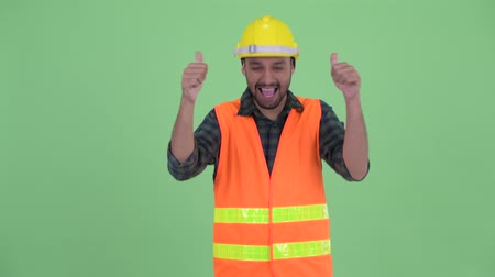 human like : Happy young bearded Persian man construction worker giving thumbs up and looking excited