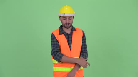 perzisch : Stressed young bearded Persian man construction worker getting bad news