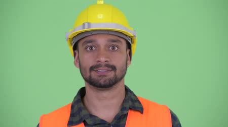 szám : Face of happy young bearded Persian man construction worker nodding head yes