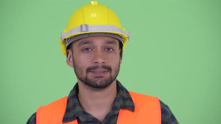 negative : Face of serious young bearded Persian man construction worker nodding head no