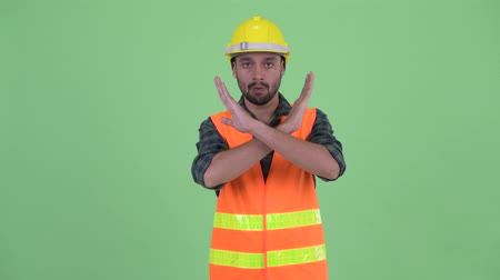 mustache : Serious young bearded Persian man construction worker with stop gesture