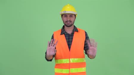 úpadek : Young bearded Persian man construction worker waving hand no