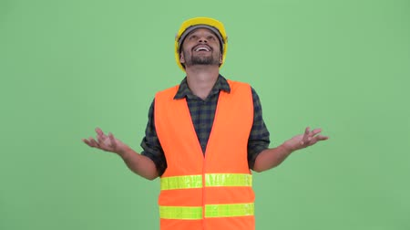 devanear : Happy young bearded Persian man construction worker catching something