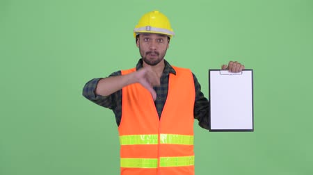 lista de verificação : Stressed young bearded Persian man construction worker showing clipboard and giving thumbs down