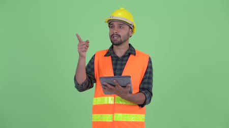directing : Happy young bearded Persian man construction worker talking while using digital tablet
