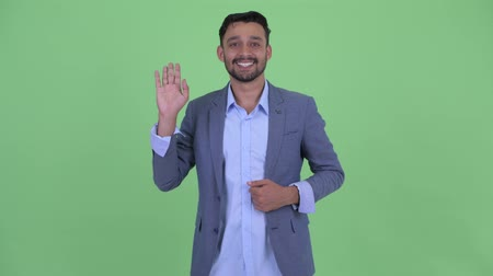 mustache : Happy young bearded Persian businessman waving hand Stock Footage