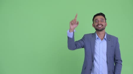 finom : Happy young bearded Persian businessman thinking and pointing up