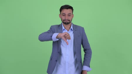 polegar : Stressed young bearded Persian businessman giving thumbs down