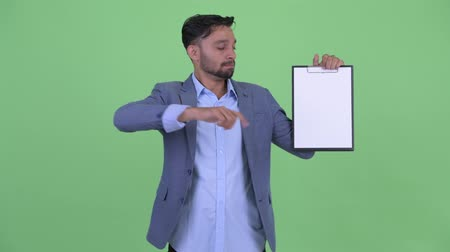 csalódott : Serious young bearded Persian businessman showing clipboard and giving thumbs down Stock mozgókép