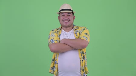 круглолицый : Happy young overweight Asian tourist man smiling with arms crossed