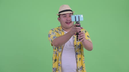 tripode : Happy young overweight Asian tourist man vlogging and showing phone Archivo de Video