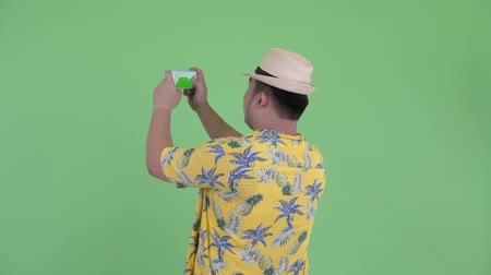 overweight : Rear view of young overweight Asian tourist man taking picture with phone Stock Footage