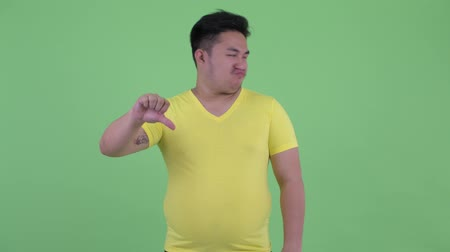 bosszús : Stressed young overweight Asian man giving thumbs down