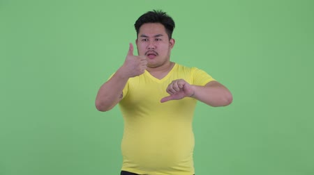 opinion : Confused young overweight Asian man choosing between thumbs up and thumbs down Stock Footage