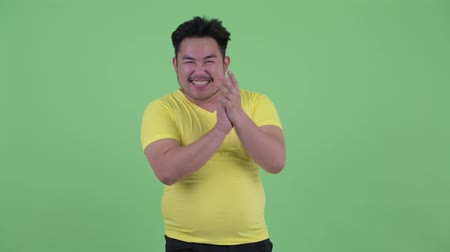 ovation : Happy young overweight Asian man clapping hands