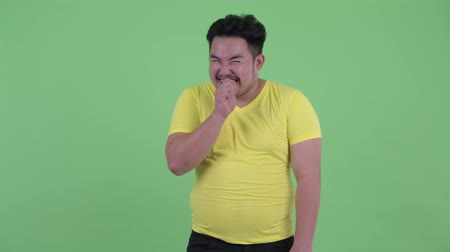 klidný : Happy young overweight Asian man with finger on lips Dostupné videozáznamy
