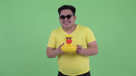 bóia : Happy young overweight Asian man holding inflatable duck ready for summer