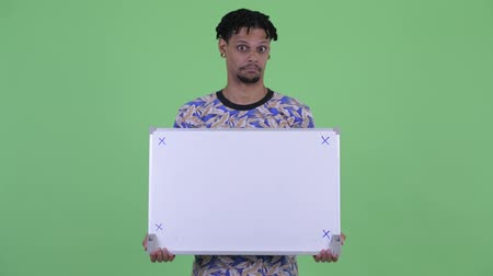 hippi : Happy young handsome African man thinking while holding white board