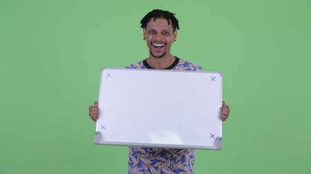 шок : Happy young handsome African man holding white board and looking surprised Стоковые видеозаписи