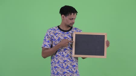 серьги : Serious young African man holding blackboard and giving thumbs down