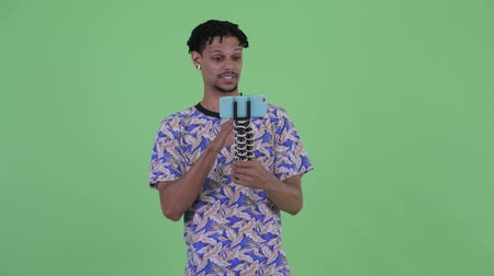 tripod shot : Happy young African man vlogging and showing phone