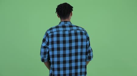 looking far away : Rear view of young African hipster man thinking and looking around Stock Footage
