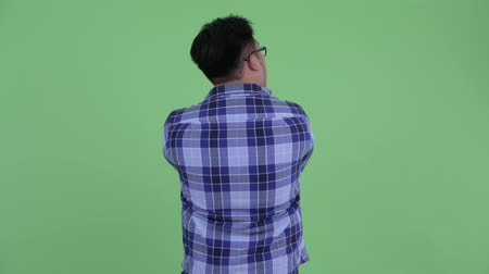 think big : Rear view of young overweight Asian hipster man thinking and looking around