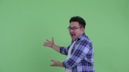 choque : Happy young overweight Asian hipster man showing to back and looking surprised