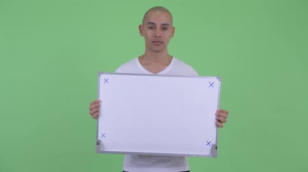 placa : Happy handsome bald man thinking while holding white board Vídeos