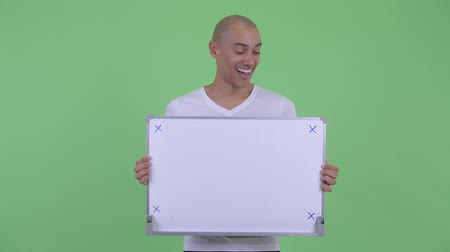 careca : Happy handsome bald man holding white board and looking surprised