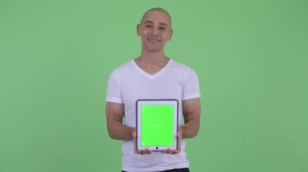 はげた : Happy handsome bald man thinking while showing digital tablet 動画素材