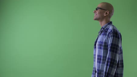 directing : Profile view of happy bald hipster man pointing finger
