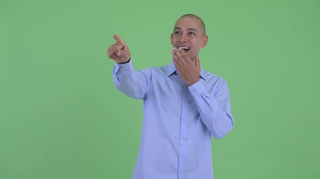 directing : Happy bald multi ethnic businessman pointing finger Stock Footage