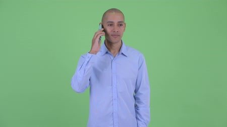 multiethnic : Happy bald multi ethnic businessman thinking while using phone and calling